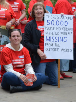 "Photo of two women wearing Missing Millions T-shirts at a protest. One is a young woman sat on the concrete. The other woman is smiling and holding a sign saying ""There's around 50,000 people housebound in the UK with ME and missing from the outside world."""