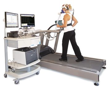 Photo of a woman walking on a treadmill while wearing a clear mask over her nose and mouth, and attached to a cart holding medical equipment.